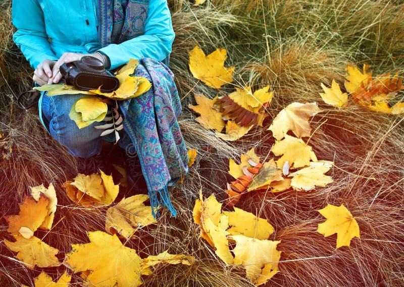 Donna che si siede con le retro foglie di autunno e della macchina fotografica immagine stock libera da diritti