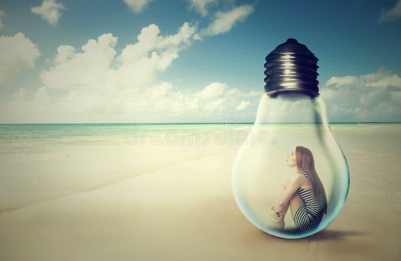 Donna che si siede dentro una lampadina su una spiaggia che esamina la vista di oceano immagini stock
