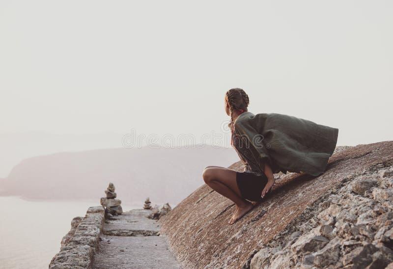 Donna che si siede e che esamina orizzonte in Monolithos, Rodi, Grecia fotografia stock libera da diritti