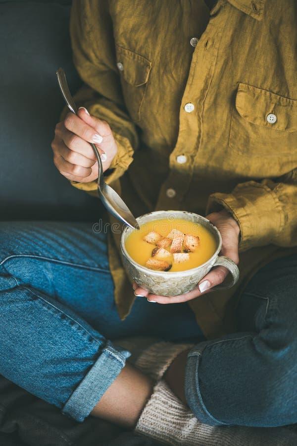 Donna che si siede e che mangia la minestra di riscaldamento della zucca dalla tazza fotografia stock