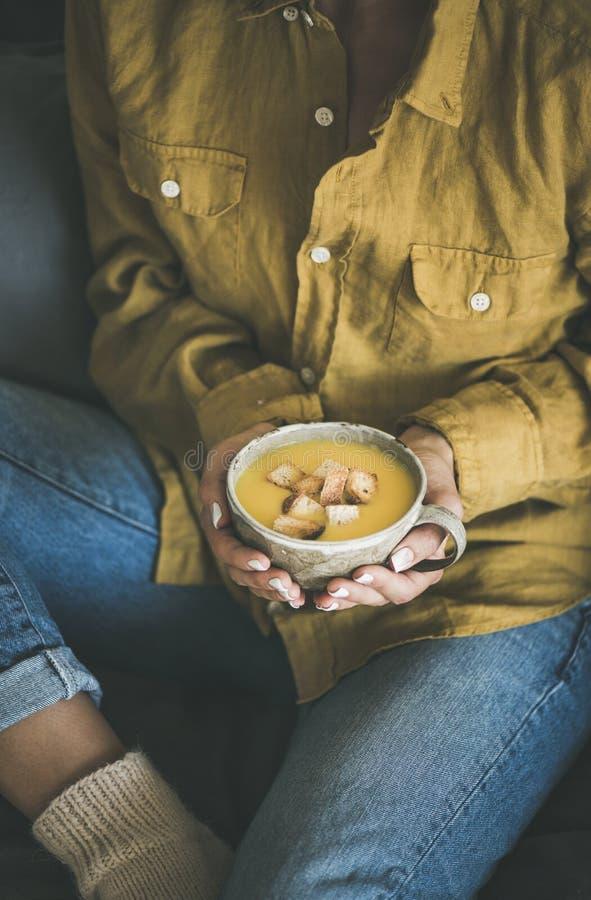 Donna che si siede e che tiene la minestra di riscaldamento della zucca in tazza immagine stock