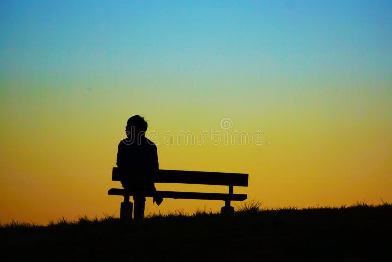 Donna che si siede la sera delle colline del banco fotografia stock libera da diritti
