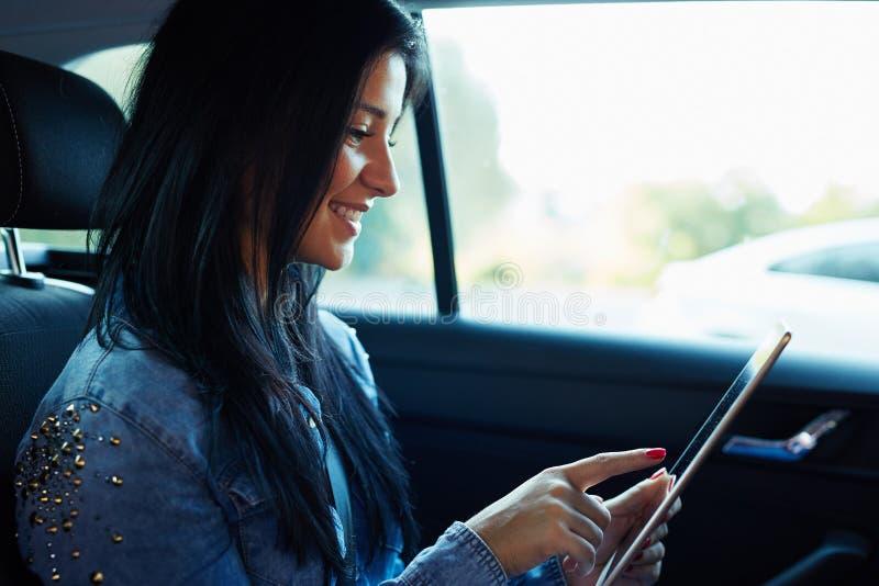 Donna che si siede nell'automobile e che per mezzo del computer digitale della compressa fotografie stock libere da diritti