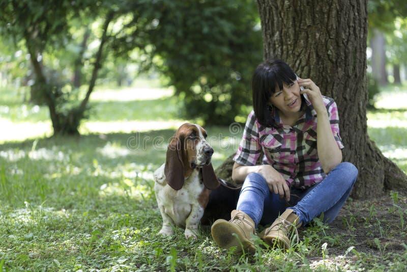 Donna che si siede nell'erba nel parco che parla sul pho mobile fotografia stock libera da diritti