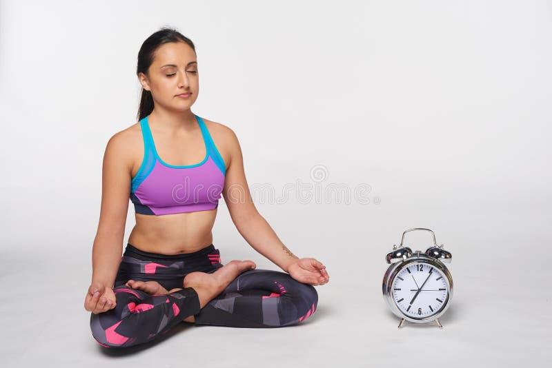 Donna che si siede nell'yoga Padmasana, posa del loto immagine stock libera da diritti