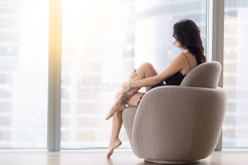 Donna che si siede nella poltrona immagini stock libere da diritti
