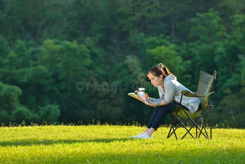 Donna che si siede nella sosta fotografia stock