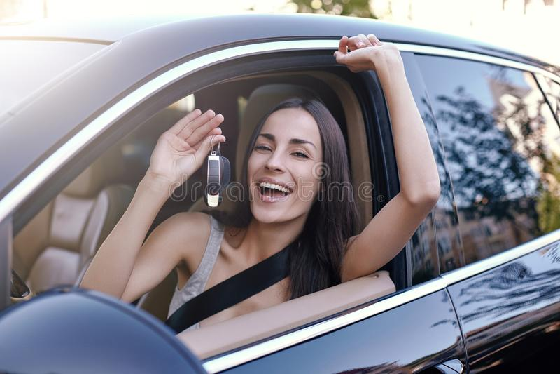 Donna che si siede in nuova automobile e che tiene le chiavi fotografia stock
