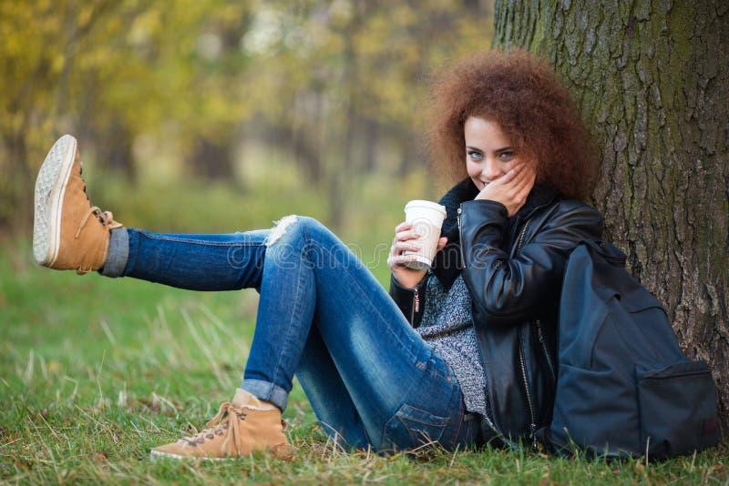 Donna che si siede sotto l'albero ed il caffè bevente nel parco di autunno fotografie stock libere da diritti