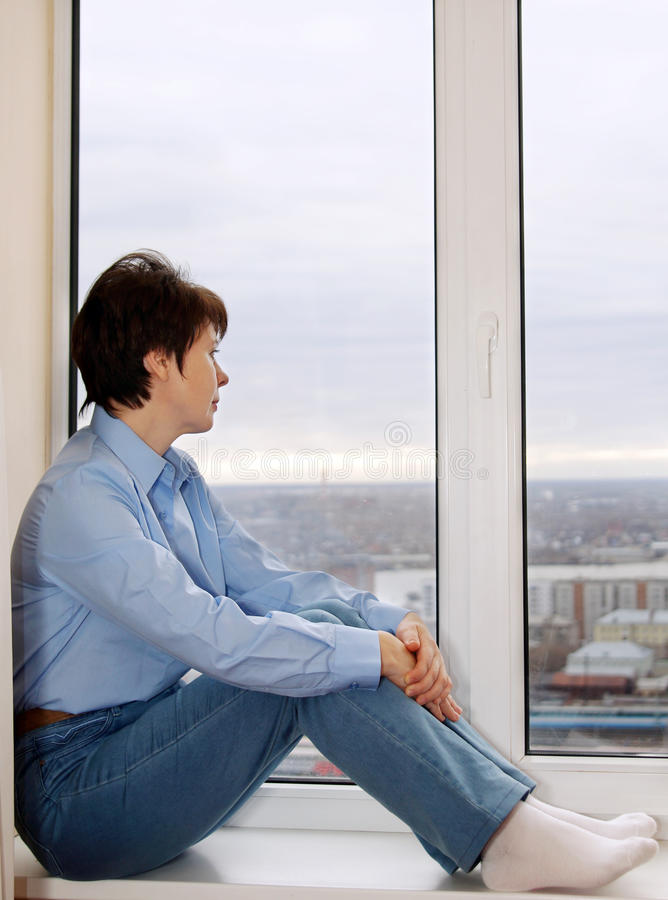 Donna che si siede su un davanzale e su un attendere immagine stock libera da diritti