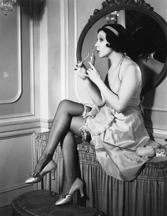 Donna che si siede su un profumo odorante di vanità da flacon (tutte le persone rappresentate non sono vivente più lungo e nessun immagini stock libere da diritti