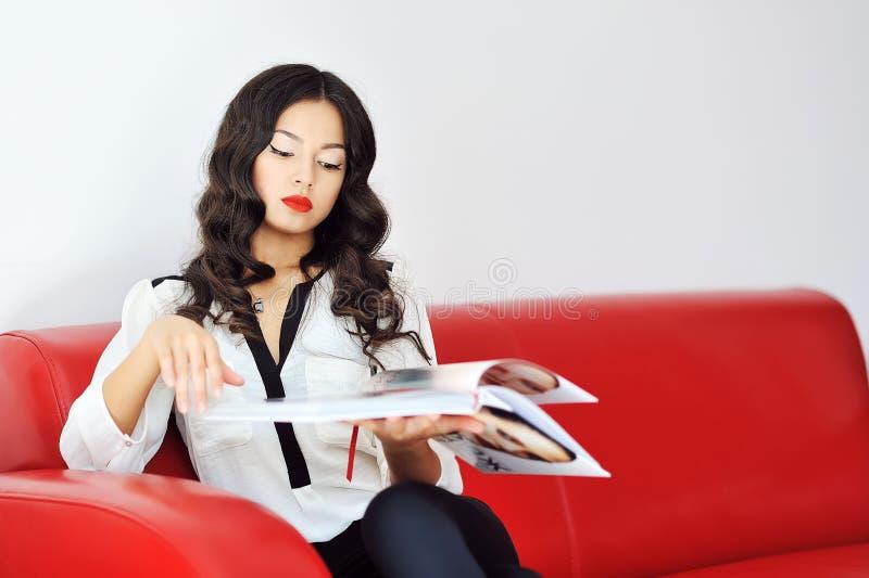 Donna che si siede su un sofà e che legge rivista immagine stock libera da diritti
