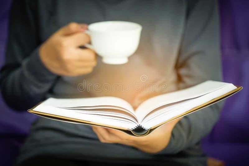 Donna che si siede su un sofà e che legge un libro fotografia stock