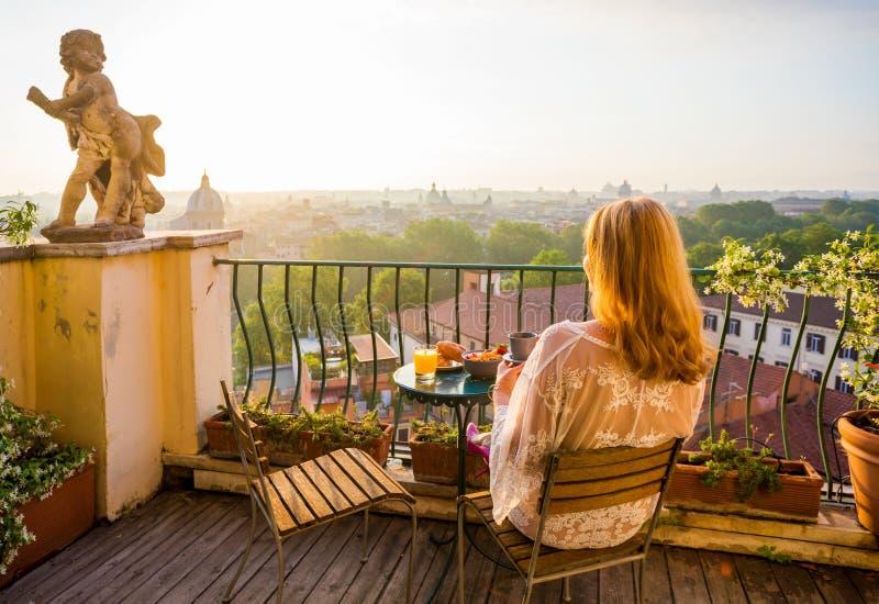 Donna che si siede sul balcone nel primo mattino fotografie stock libere da diritti