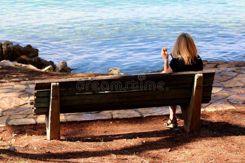 Donna che si siede sul banco di legno e che mangia panino accanto al percorso di pietra tradizionale dal mare che gode della vist immagine stock