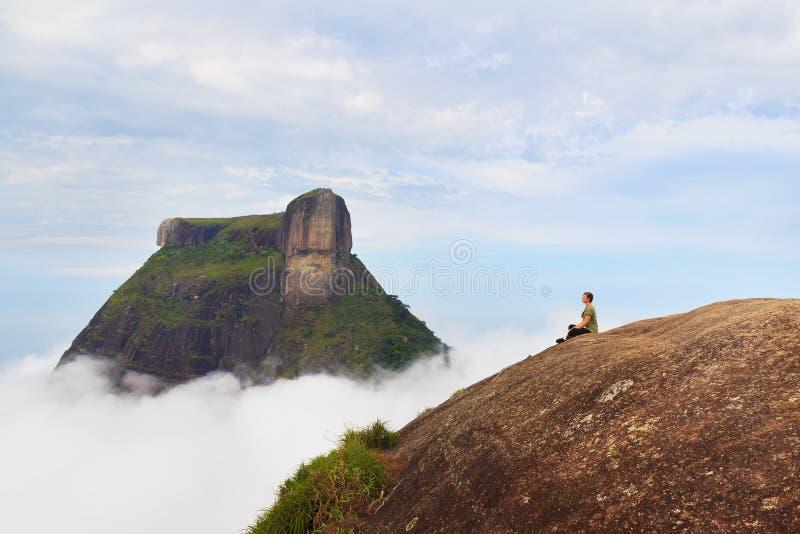 Donna che si siede sul bordo della montagna Pedra Bonita, Rio de Janeiro, immagine stock libera da diritti