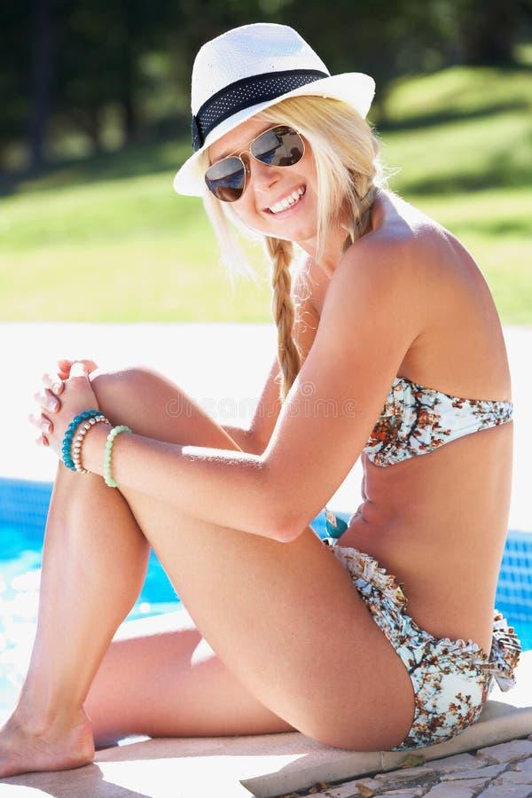 Donna Che Si Siede Sul Bordo Di Nuoto Nel Raggruppamento Fotografia Stock Libera da Diritti