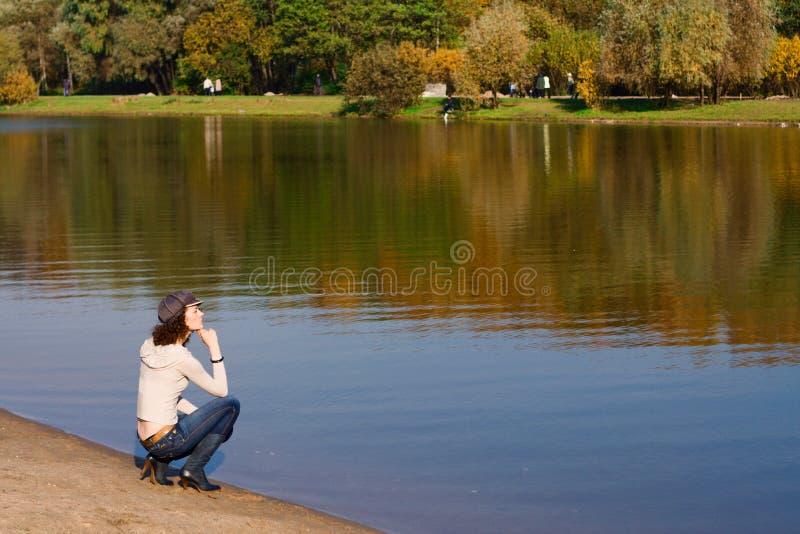 Donna che si siede sul bordo di un fiume immagine stock libera da diritti