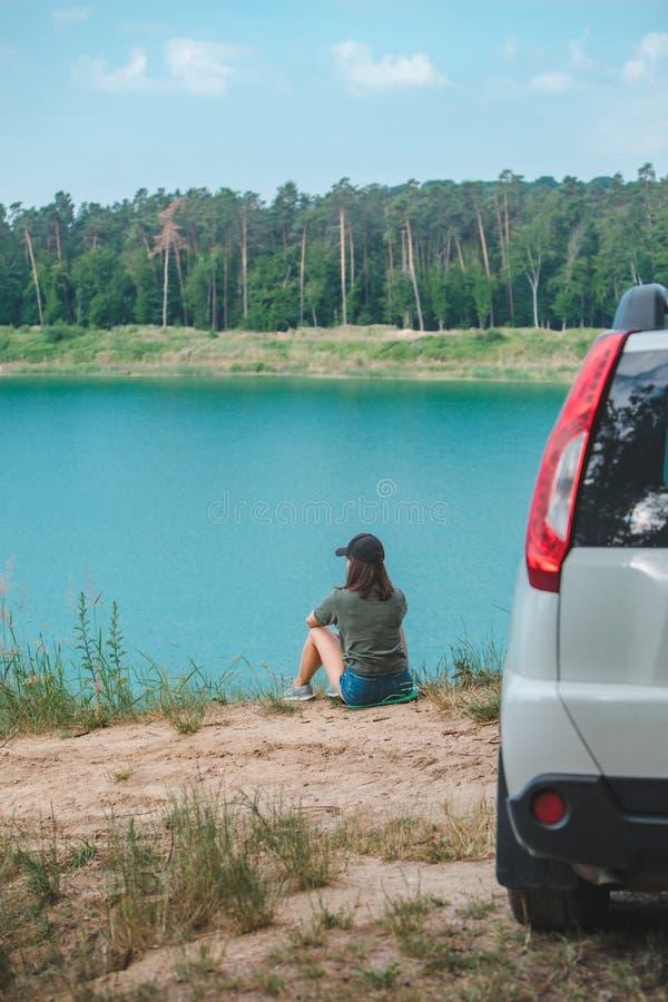 Donna che si siede sul bordo che gode della vista del lago immagine stock