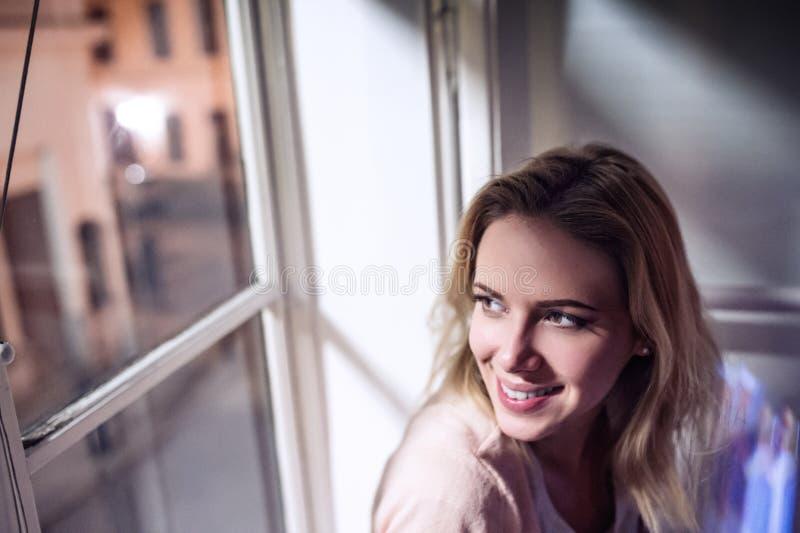 Donna che si siede sul davanzale, guardando dalla finestra, sorridente immagini stock libere da diritti