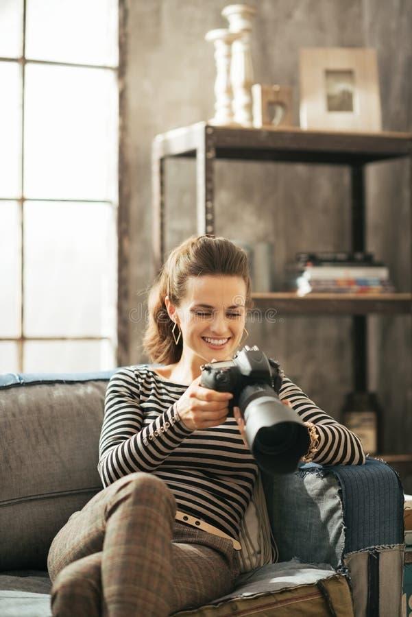 Donna che si siede sul divano e che usando la macchina fotografica della foto del dslr fotografia stock