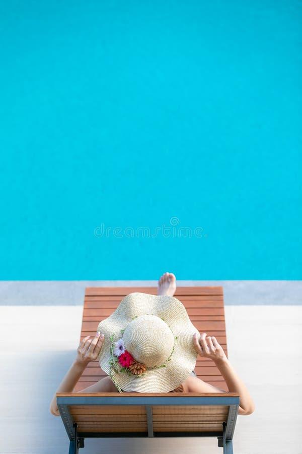 Donna che si siede sul letto accanto alla piscina fotografia stock libera da diritti