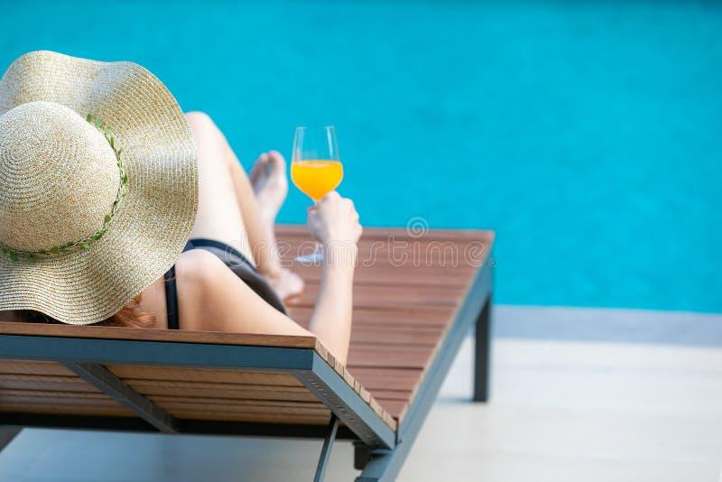 Donna che si siede sul letto accanto alla piscina immagini stock