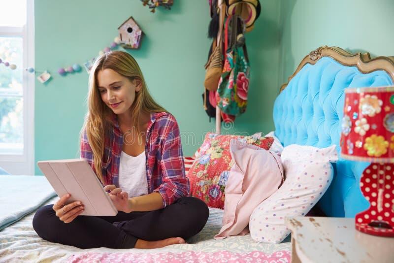 Donna che si siede sul letto a casa facendo uso della compressa di Digital fotografie stock libere da diritti