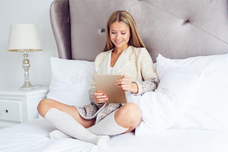 Donna che si siede sul letto con la sua compressa fotografia stock