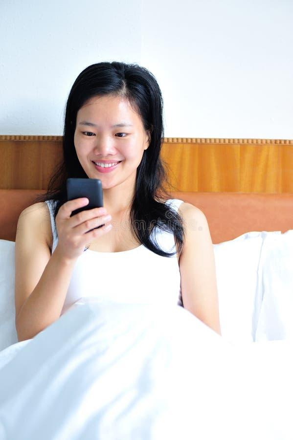Donna che si siede sul letto facendo uso del suo smartphone immagine stock