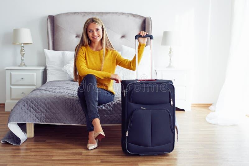 Donna che si siede sul letto in una camera di albergo fotografia stock