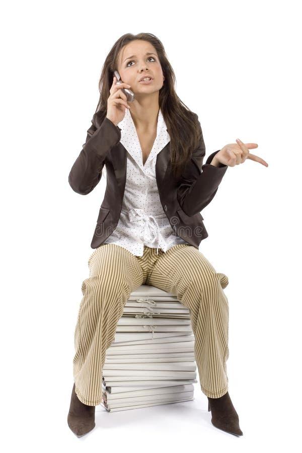 Donna che si siede sul mucchio degli archivi, telefono mobile di conversazione immagine stock