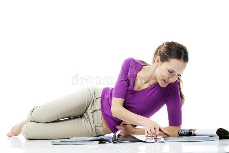 Donna che si siede sul pavimento che legge uno scomparto fotografia stock libera da diritti