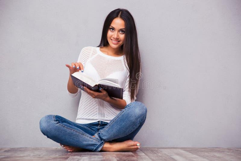 Donna che si siede sul pavimento con il libro fotografia stock