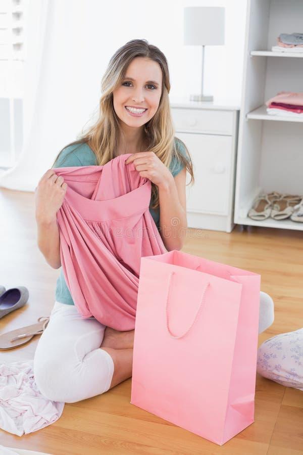 Donna che si siede sul pavimento con il nuovi vestito e sacchetto della spesa fotografia stock