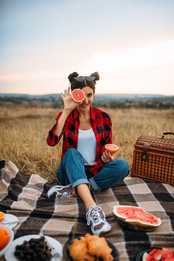 Donna che si siede sul plaid, picnic nel campo di estate fotografia stock libera da diritti