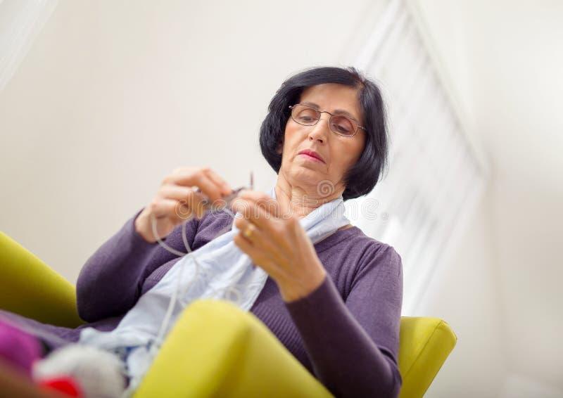 Donna che si siede sul tricottare della poltrona fotografia stock