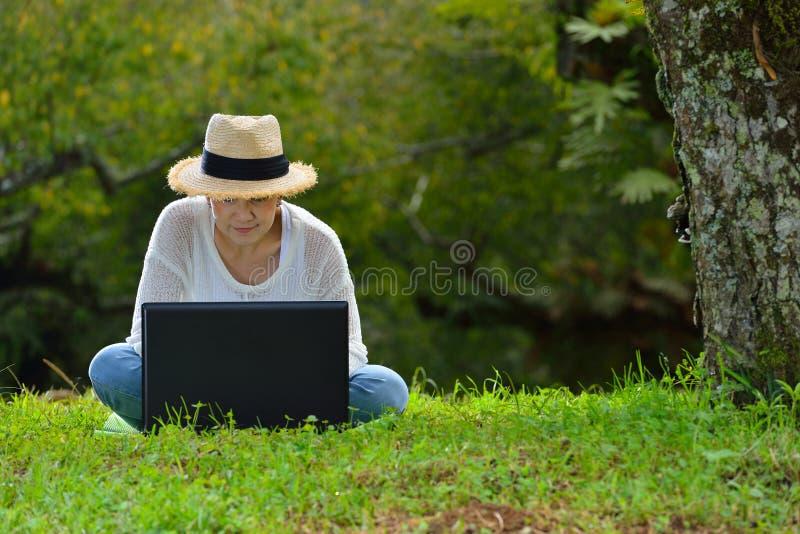 Donna che si siede sull'erba verde facendo uso del computer portatile fotografia stock