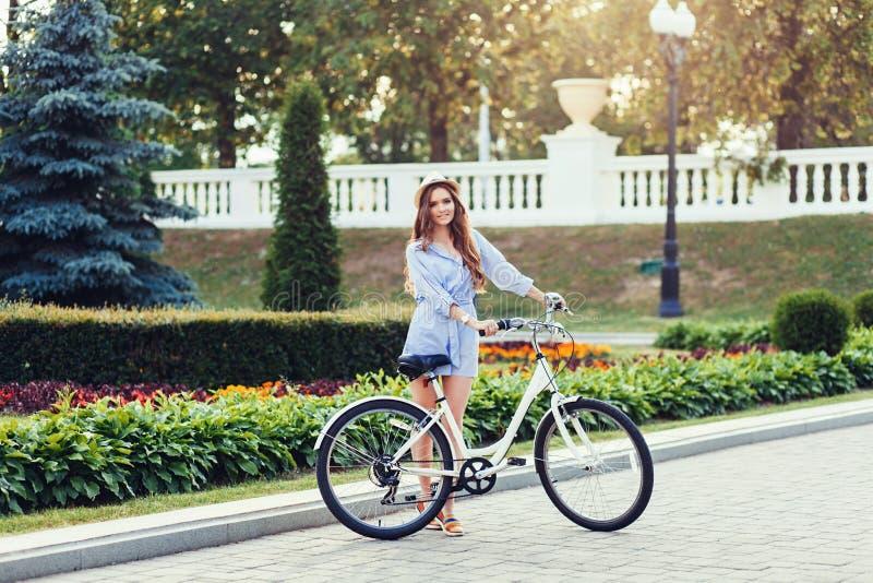 Donna che si siede sulla bicicletta in vecchia città immagine stock