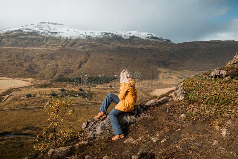Donna che si siede sulla scogliera rocciosa e che esamina stupente paesaggio nordico, Islanda Viaggio e natura immagini stock libere da diritti