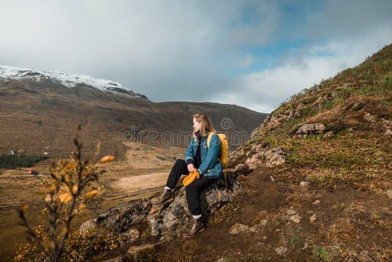 Donna che si siede sulla scogliera rocciosa e che esamina stupente paesaggio nordico, Islanda Viaggio e natura fotografie stock libere da diritti