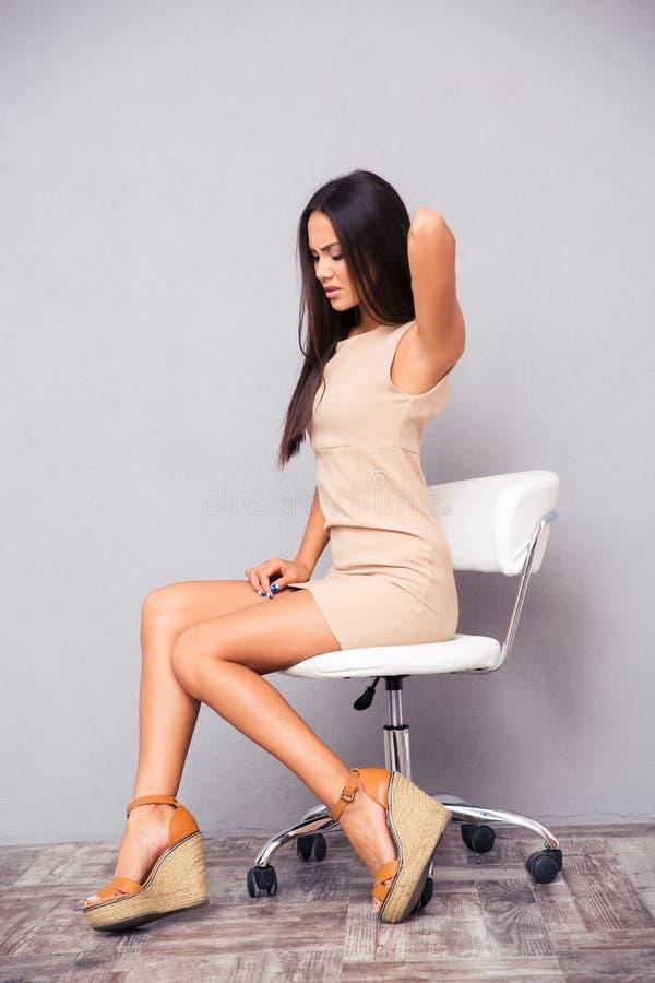 Donna che si siede sulla sedia dell'ufficio con backpain fotografia stock libera da diritti