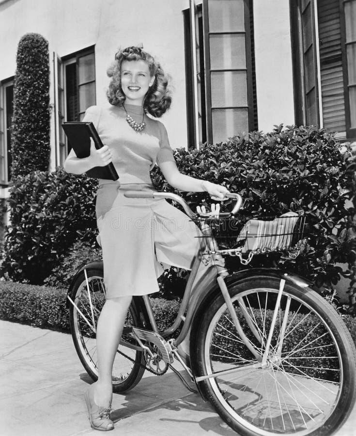 Donna che si siede sulla sua bicicletta con un libro in lei armi (tutte le persone rappresentate non sono vivente più lungo e nes immagini stock