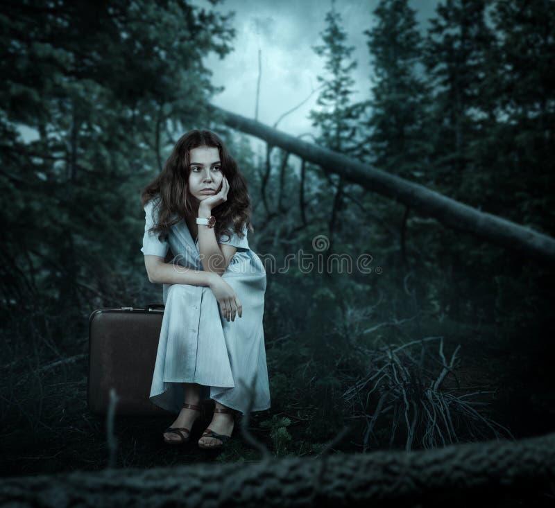 Donna che si siede sulla sua valigia nella foresta immagine stock libera da diritti