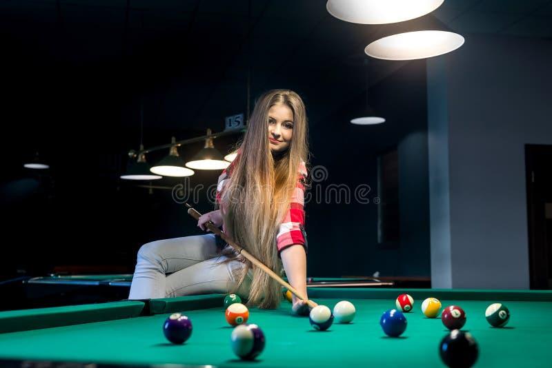 Donna che si siede sulla tavola di biliardo e sulla palla colpita andante fotografie stock libere da diritti