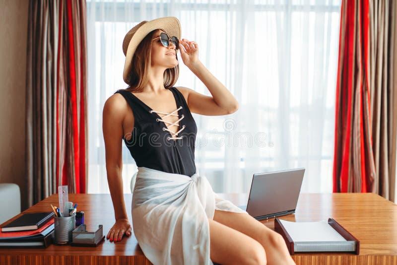 Donna che si siede sulla tavola, pensante all'avventura immagine stock