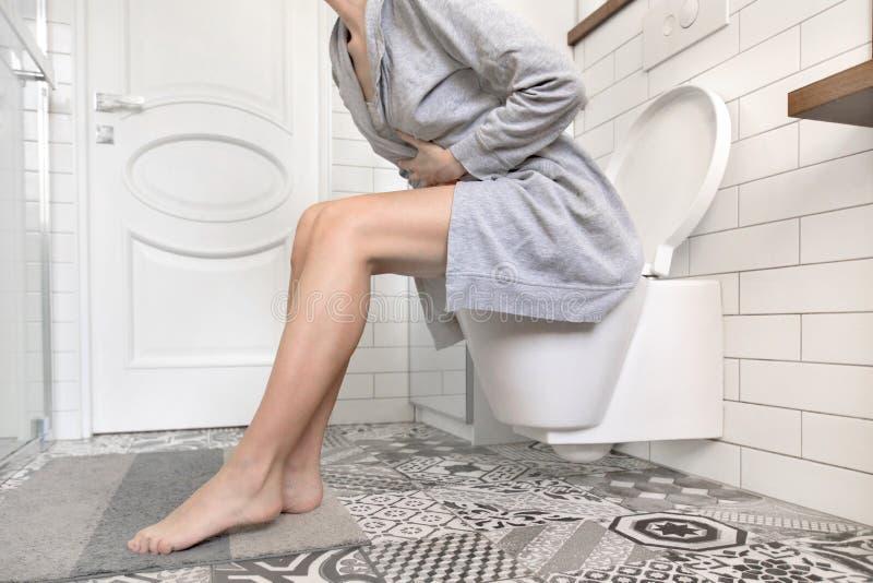 Donna che si siede sulla toilette che tiene il suo stomaco fotografie stock libere da diritti