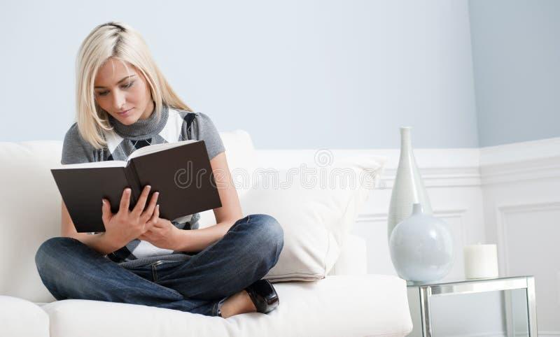 Donna che si siede sullo strato e che legge un libro fotografia stock