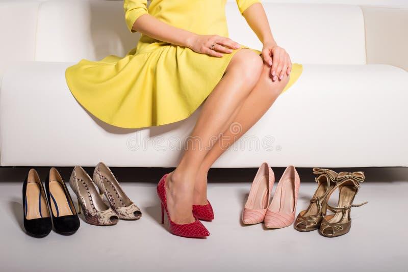 Donna che si siede sullo strato e che sceglie che scarpe per durare fotografie stock