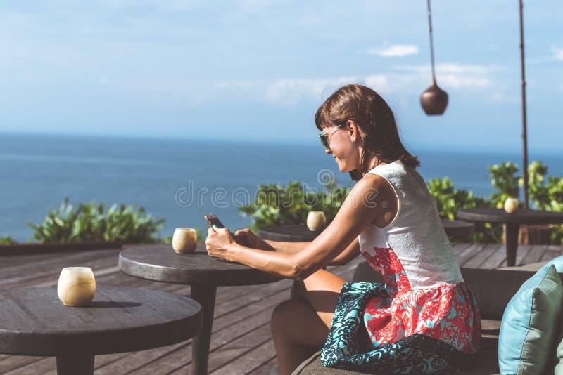 Donna che si siede in un ristorante tropicale con la vista di oceano Posto originale Spazio per testo Isola di Bali fotografia stock libera da diritti